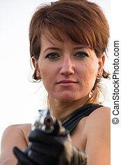 Young woman on a white background to aim a pistol