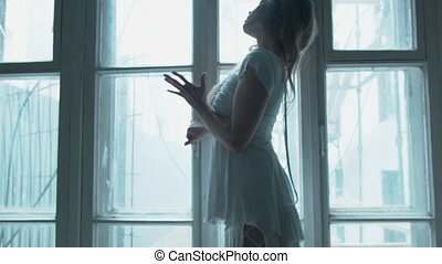 Young woman on against a window in a white dress and in a mesh pantyhose dancing slowly. The blonde stands on the poddokonike and raises her hand up.