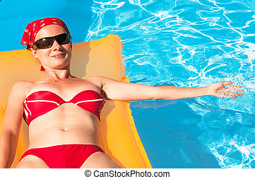 Young woman on an orange inflatable