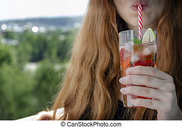 young woman on balcony drinks cold fresh strawberry mojito
