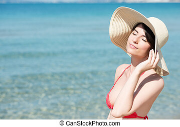 Young woman on beach enjoying the sun