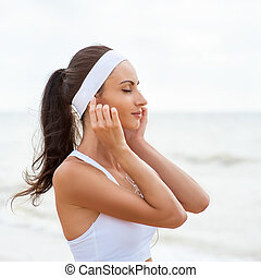 Young woman on beach listening to music in earphones from smart phone mp3 player smartphone armband