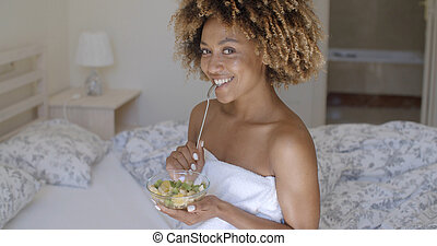 Young Woman On Bed Eating Vegetable Salad