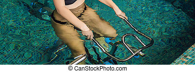 Young woman on bicycle simulator underwater in the pool BANNER, long format