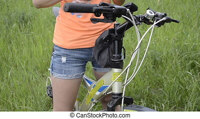Young woman on bike drinking water