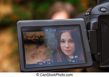 Young woman on camera screen looking at camera