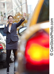 Young Woman on Cell Phone Hailing a Yellow Taxi Cab - A...