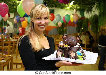 young woman on children's holiday in kindergarten with chocolate