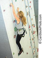 Young woman on climbing wall