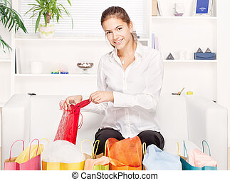young woman on couch with shopping bags