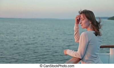 Young woman on cruise ship at sunset.