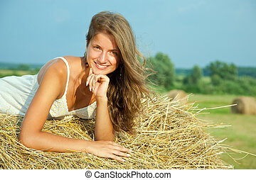 Young woman  on hay bail