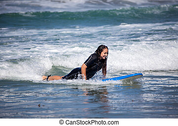 young woman on her surfboard