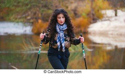 Young woman on hiking. Scandinavian walk. Forest