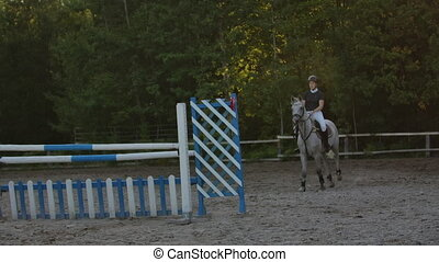 Young woman on horse jumping over obstacles. Slow motion....