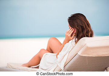 Young woman on lounger with mobile phone at the beach