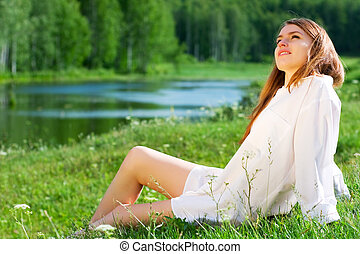 Young woman on nature - Young woman relaxing on the shore of...