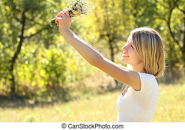 young woman on nature with a bouquet of flowers