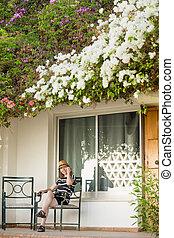 Young woman on phone on veranda