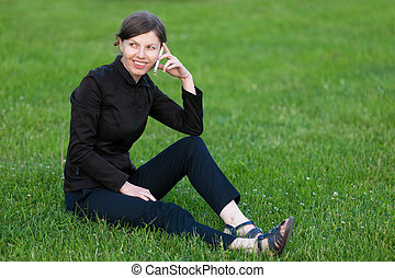 Young woman on phone sitting on grass