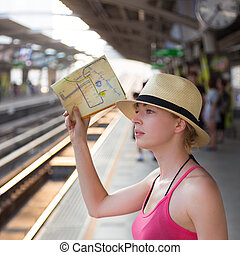 Young woman on platform of railway station.