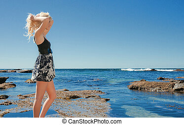 young woman on reef at sea