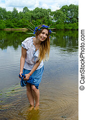Young woman on river bank squeezes wet hem of skirt