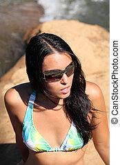 Young woman on riverbank sunglasses and bikini top