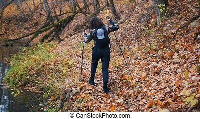 Young woman on scandinavian walk in the forest. Woman gets...