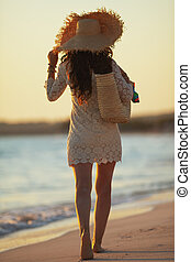young woman on seacoast at sunset walking