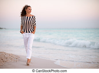 young woman on seashore in evening walking