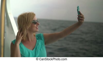 Young woman on ship desk taking selfie