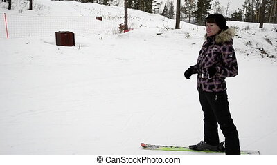 Young woman on skis pulls the phone