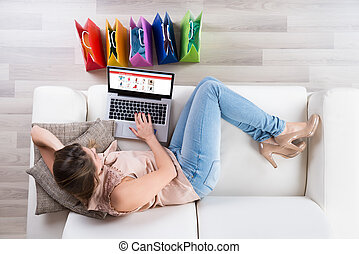 Woman On Sofa Shopping Online With Laptop