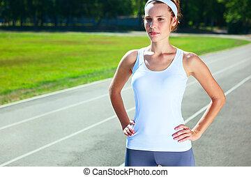 Young woman on stadium preparing herself for marathon run.