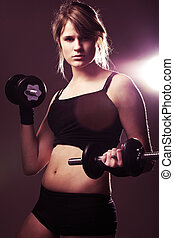 young woman on studio doing her workout welghtlifting dumbbell