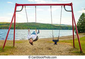 Young woman on swing in Oppstrynsvatn lake in the municipality of Stryn in Sogn og Fjordane county, Norway