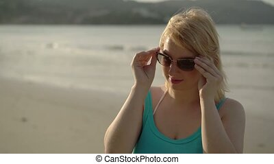 Young woman on the beach wearing sunglasses