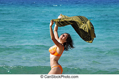 Young woman on the beach with a colored tissue