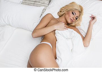 Young woman on the bed - Pretty young woman laying on the...