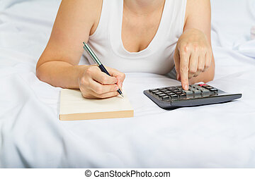 young woman on the bed with a notebook and calculator Credit, mortgage.