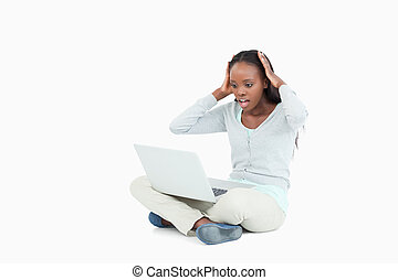 Young woman on the floor surprised by her laptop