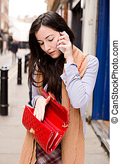 young woman on the phone lookinbg in her bag