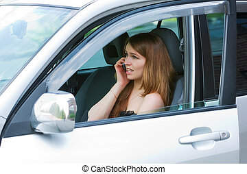 Young woman on the phone sitting in a car.