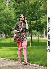 Young Woman on the Phone Walking in a Park