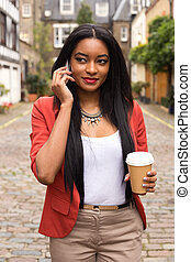 young woman on the phone with a coffee