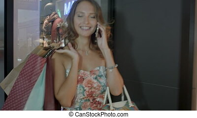 Young woman on the phone with shopping bags in the mall.