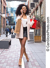 young woman on the phone with shopping bags