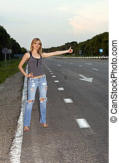 Young woman on the roadside - Young woman with a raised arm ...