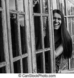 Young woman on the veranda of a country house, black-and-white photo.